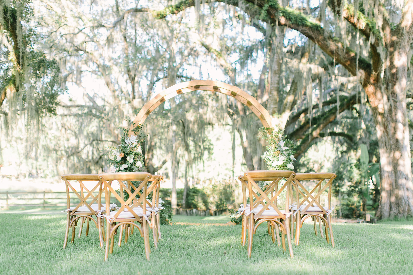 Outdoor Florida At Home Front Back Yard Wedding Ceremony | Round Wood Moon Arch Wedding Ceremony Backdrop with Natural Ivory and Peach Garland Floral Arrangements | Wood French Country Cross Back Chairs with Ivory Cushions | Intimate COVID Social Distancing Wedding