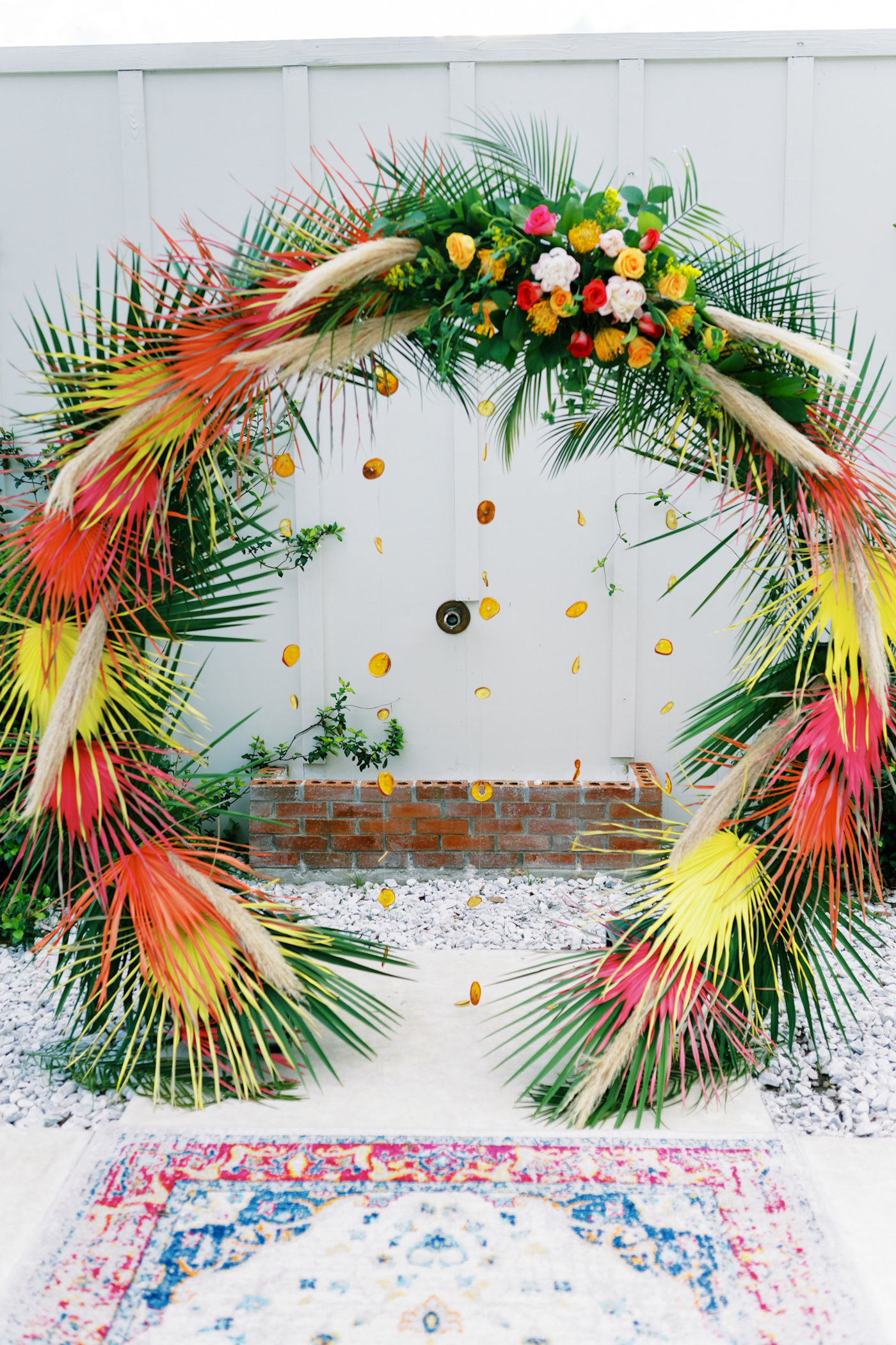 Tropical Florida Citrus Wedding Inspiration | Orange and Yellow Painted Palm Frond Leaf Round Moon Arch Ceremony Backdrop with Pampas Grass and Hanging Orange Slices