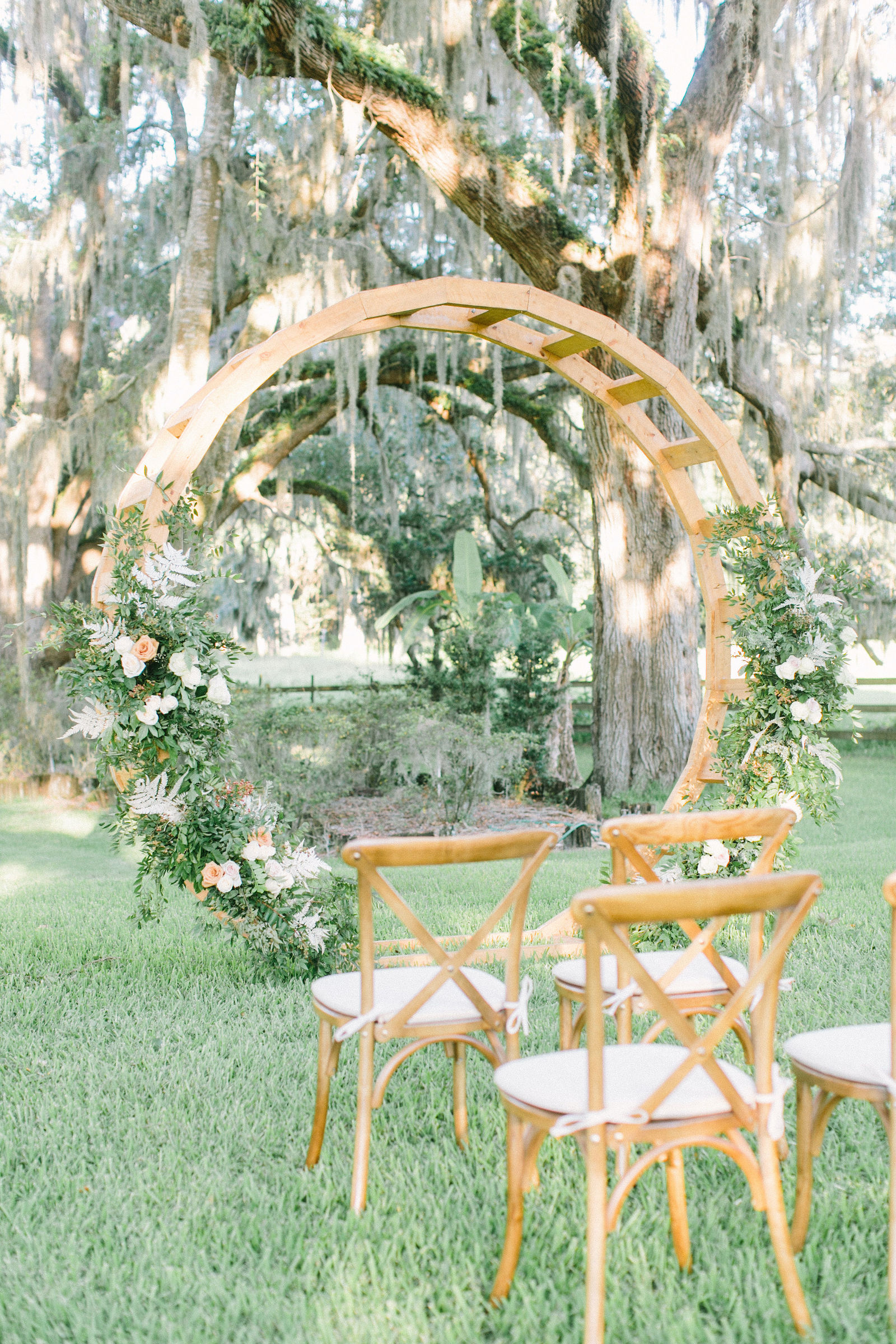 Outdoor Florida At Home Front Back Yard Wedding Ceremony | Round Wood Moon Arch Wedding Ceremony Backdrop with Natural Ivory and Peach Garland Floral Arrangements | Wood French Country Cross Back Chairs with Ivory Cushions