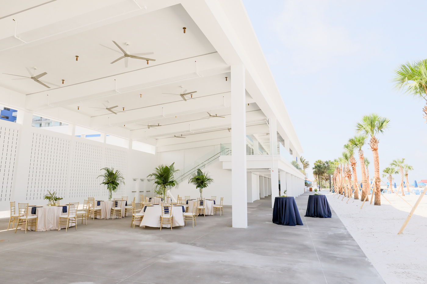 Clearwater Beach Wedding Venue Hilton Clearwater Beach   Modern Tropical Beach Outdoor Wedding Reception Terrace with White Table Linens and Gold Chiavari Chairs and Champagne Sash Bows and Tropical Palm Frond Leaf Floral Arrangement Centerpieces