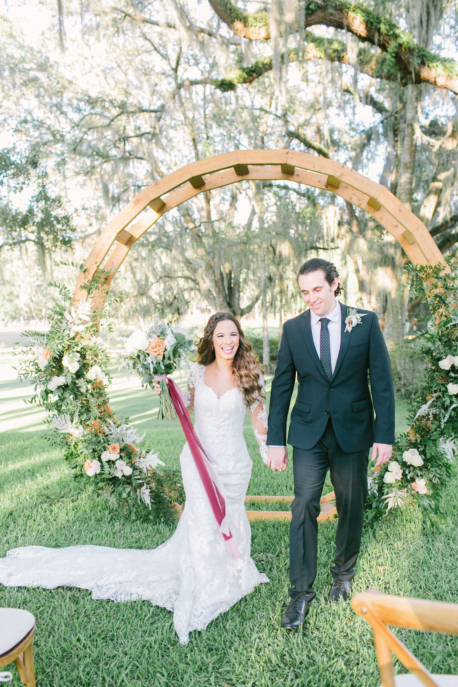 Outdoor Florida Bride and Groom Wedding Portrait | Groom Wearing Classic Black Suit Tux | Lace Mermaid Long Sleeve Low Back Illusion Lace Bridal Gown Wedding Dress | Ivory Champagne and Peach Natural Bouquet with Roses Astilbe and Greenery tied with Blush Pink and Mauve Ribbons | Round Wood Moon Arch Wedding Ceremony Backdrop with Natural Ivory and Peach Garland Floral Arrangements