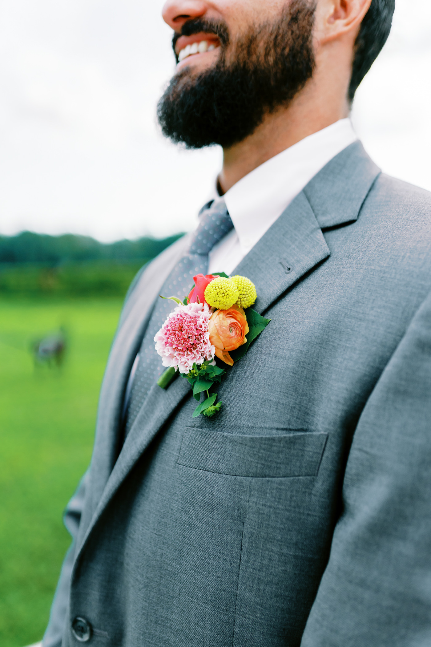 Bright Colorful Boutonniere with Pink Scabiosa Orange Ranunculus and Yellow Crespedia Billy Ball | Groom in Grey Suit