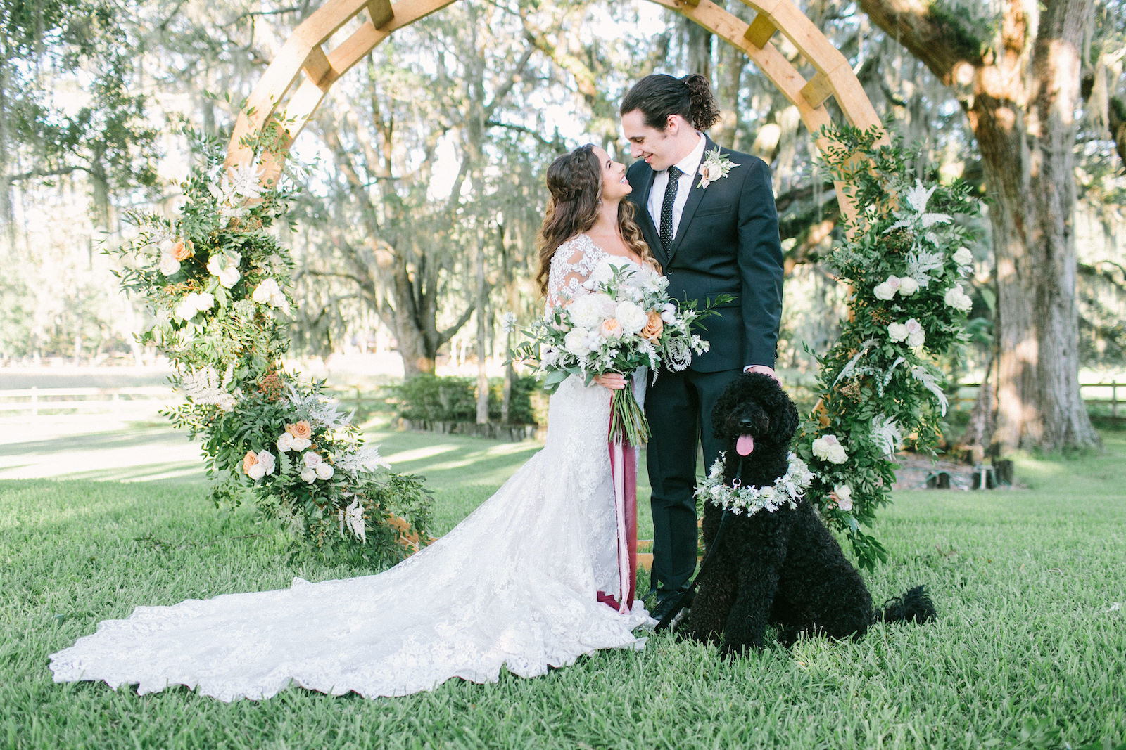 Outdoor Florida Bride and Groom Portrait with Pet Dog Labradoodle | Best Dog of Honor with Floral Collar | Groom Wearing Classic Black Suit Tux | Lace Mermaid Long Sleeve Low Back Illusion Lace Bridal Gown Wedding Dress | Ivory Champagne and Peach Natural Bouquet with Roses Astilbe and Greenery tied with Blush Pink and Mauve Ribbons | Round Wood Moon Arch Wedding Ceremony Backdrop with Natural Ivory and Peach Garland Floral Arrangements