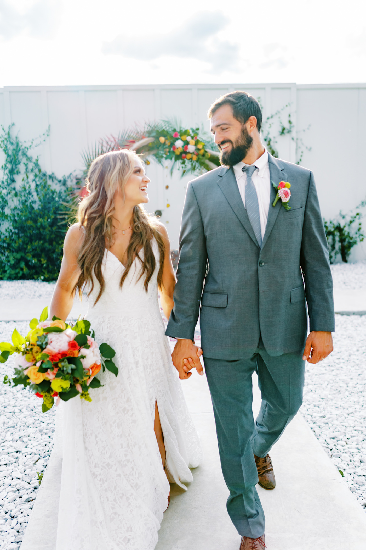 Bright Colorful Florida Citrus Wedding Inspiration | Bridal Bouquet with Pink Orange and Yellow Roses | Groom in Grey Suit with Grey Neck Tie