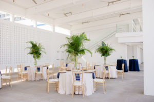 Clearwater Beach Wedding Venue Hilton Clearwater Beach | Modern Tropical Beach Outdoor Wedding Reception Terrace with White Table Linens and Navy Napkins under Gold Charger Plates | Gold Chiavari Chairs and Champagne Sash Bows and Tropical Palm Frond Leaf Floral Arrangement Centerpieces