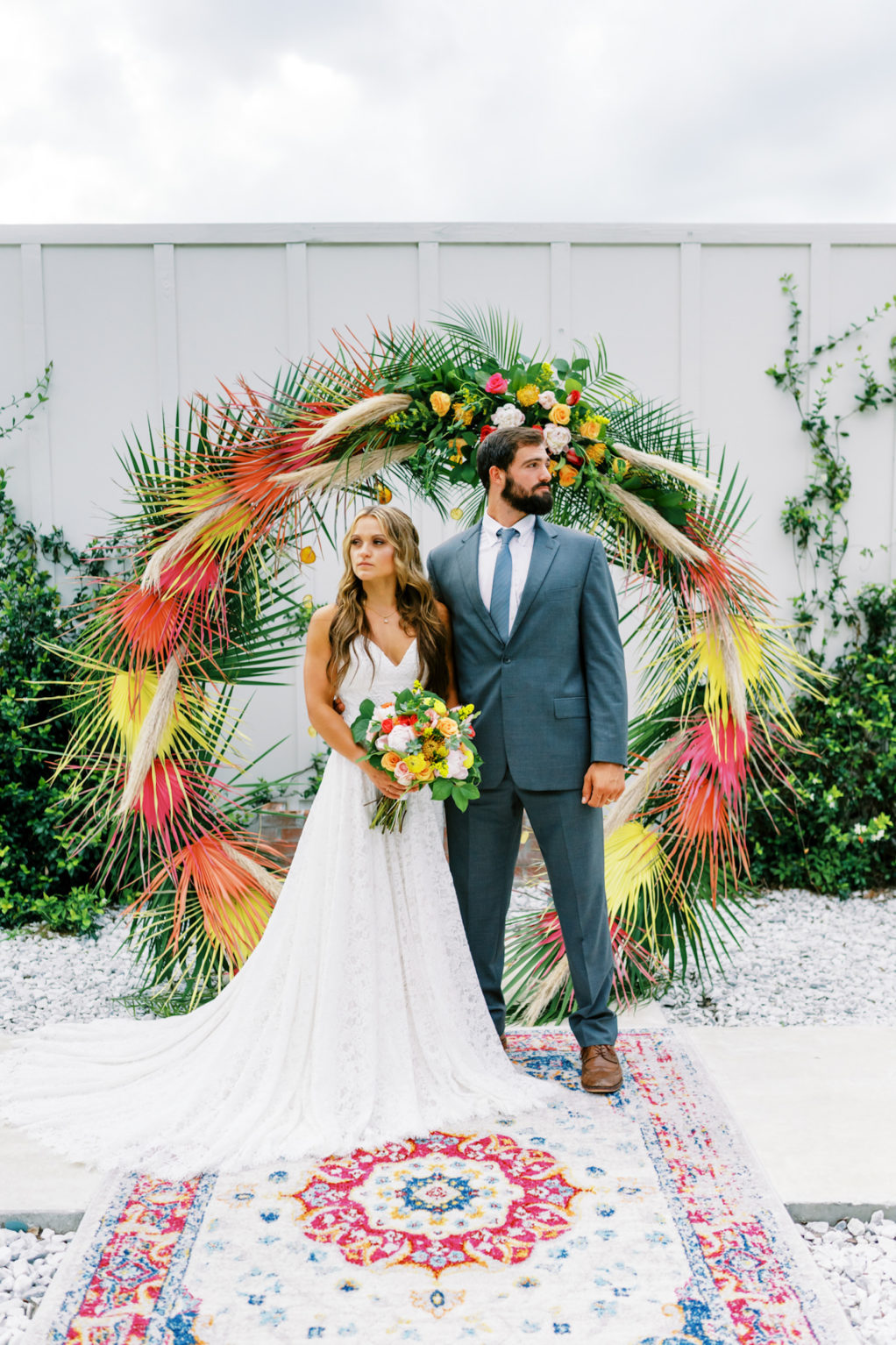 Tropical Florida Citrus Wedding Inspiration | Orange and Yellow Painted Palm Frond Leaf Round Moon Arch Ceremony Backdrop with Pampas Grass and Hanging Orange Slices | Bright Colorful Floral Arrangement with Orange and Pink Roses and Yellow Pincushion Protea | Ceremony Area Rug | Groom in Grey Suit