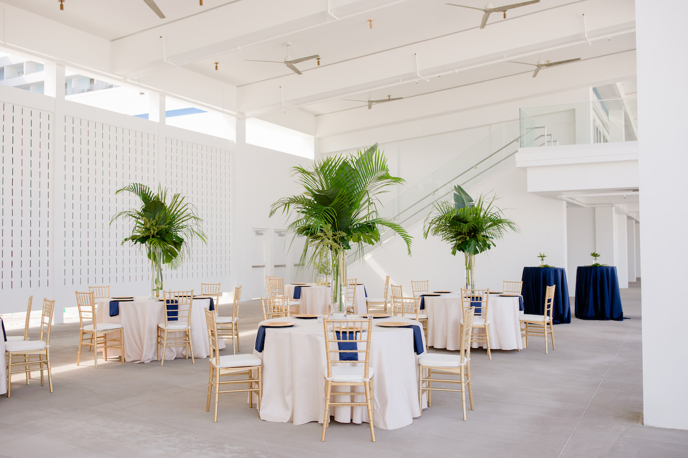 Clearwater Beach Wedding Venue Hilton Clearwater Beach   Modern Tropical Beach Outdoor Wedding Reception Terrace with White Table Linens and Navy Napkins under Gold Charger Plates   Gold Chiavari Chairs and Champagne Sash Bows and Tropical Palm Frond Leaf Floral Arrangement Centerpieces