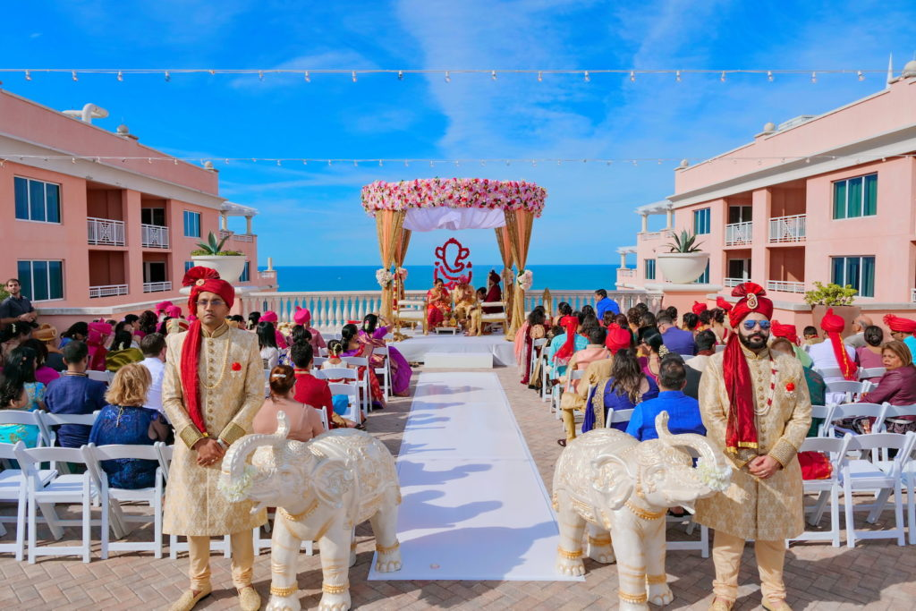 Rooftop Indian Wedding Ceremony at Clearwater Wedding Venue Hyatt Regency Clearwater Beach | Ivory and Gold Elephant Statues at Ceremony Aisle | Pink and Gold Mandap with Draping and Roses