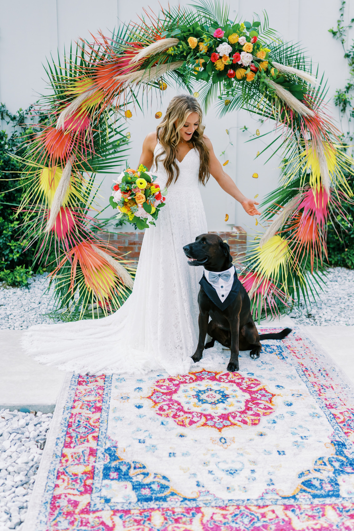 Tropical Florida Citrus Wedding Inspiration | Orange and Yellow Painted Palm Frond Leaf Round Moon Arch Ceremony Backdrop with Pampas Grass and Hanging Orange Slices | Bright Colorful Floral Arrangement with Orange and Pink Roses and Yellow Pincushion Protea | Ceremony Area Rug | Wedding Dog of Honor with Bow Tie Collar