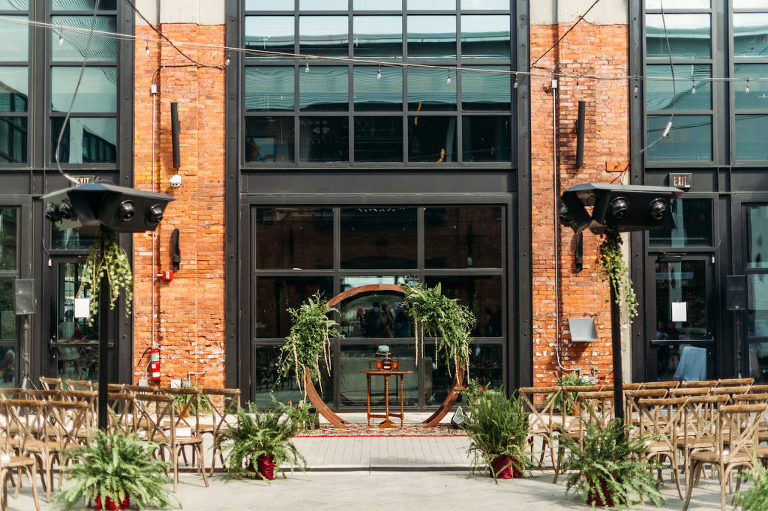 Tampa Wedding Armature Works Courtyard Ceremony with Canopy String Lights and Wood Cross Back Chairs and Round Moon Arch | Ceremony Aisle with Potted Ferns and Greenery Wedding Floral Arrangements | Outdoor Tampa Weddings