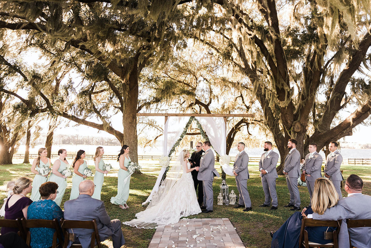 Rustic Elegant Outdoor Wedding Ceremony and Decor, Florida Bride and Groom Exchange Vows Under Wooden Arch, Crucifix Cross Backdropm White Draping with Eucalyptus Leaf Greenery, Vintage Ivory Bird Cages, Bridesmaids in Long Sage Green Dresses | Tampa Bay Luxury Wedding Planner and Floral Designer John Campbell Weddings | Covington Farm