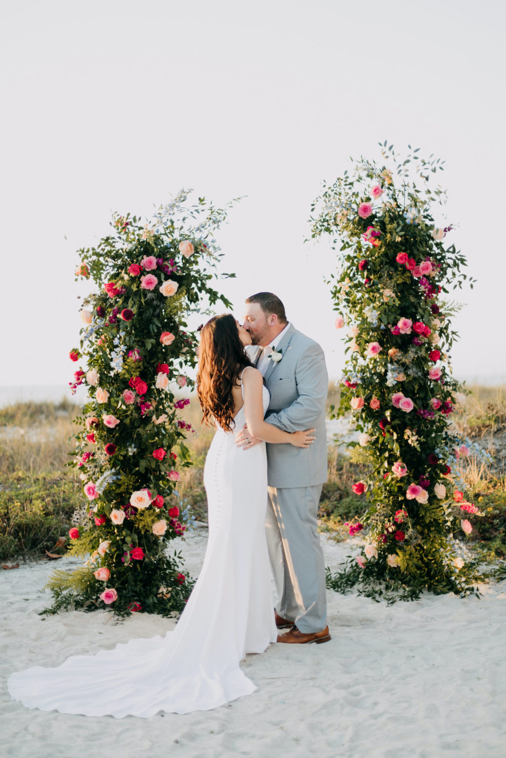 Blush Pink and Fuchsia Roses and Greenery Wedding Ceremony Backdrop Arrangements | Bride and Groom and Son at Tampa St Pete Florida COVID Destination Elopement Beach Wedding Ceremony | Amber McWhorter Photography