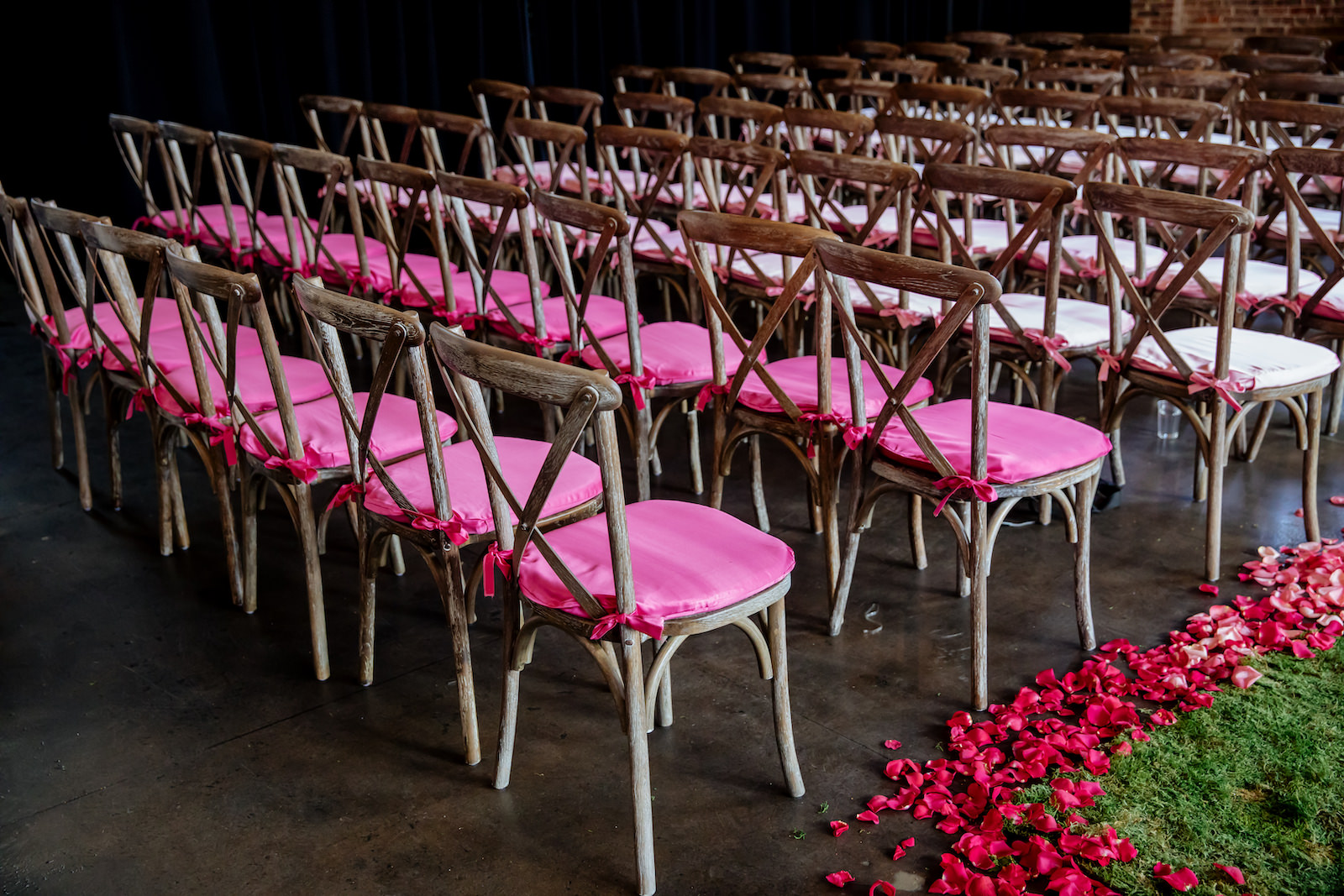 Modern Wedding Ceremony with Moss Aisle Runner with Ombre Pink and White Rose Petals   Wood Cross Back Chairs with Ombre Pink Cushion Covers