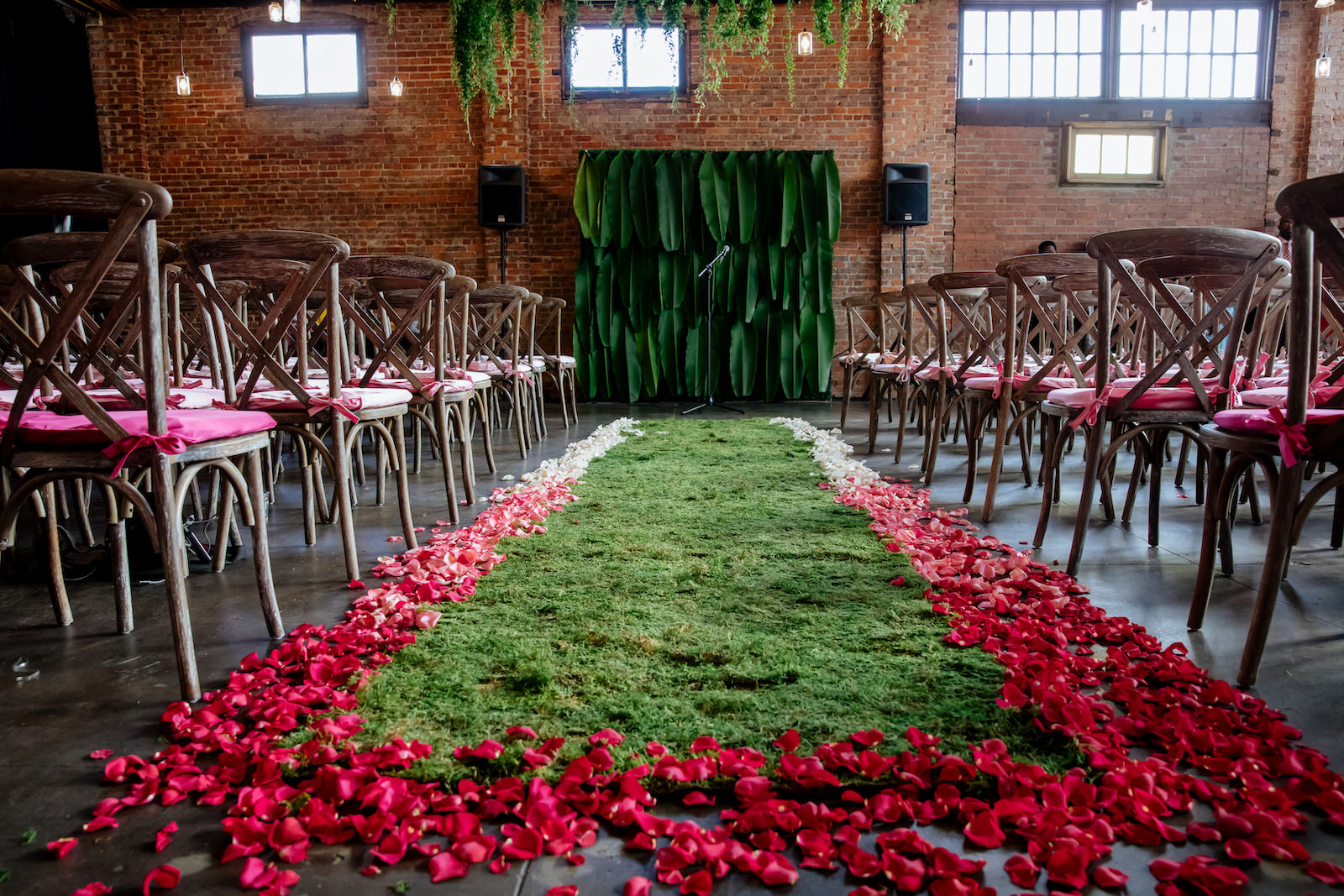 Modern Wedding Ceremony Backdrop with Tropical Palm Leaves and Moss Aisle Runner with Ombre Pink and White Rose Petals   Wood Cross Back Chairs and Historic Brick Walls   Suspended Greenery Garland Ceiling Installment Wedding Floral Chandelier