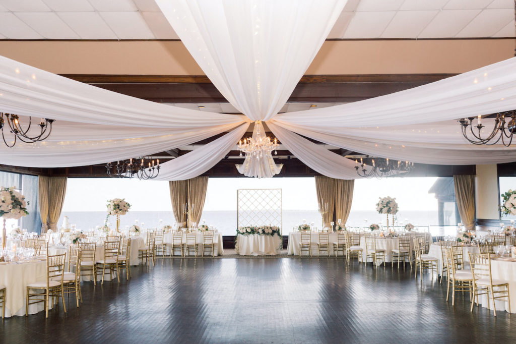 Classic Elegant Wedding Reception Decor, White Ceiling Draping, Chandeliers, Gold Chiavari Chairs, Low and Tall Floral Centerpieces | Tampa Bay Wedding Planner Special Moments Event Planning | Tampa Bay Wedding Reception Venue The Rusty Pelican