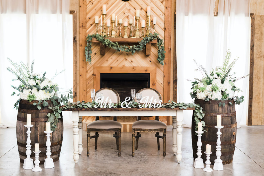 Rustic Chic Wedding Reception and Decor, Antique Farmhouse Sweetheart Table with Mr. and Mrs. Wooden Cut Out, Green Eucalyptus Leaf Garland, White Roses, Ivory Florals and Greenery | Covington Farm | Florida Wedding Planner and Floral Designer John Campbell Weddings | Tampa Bay Caterer Olympia Catering