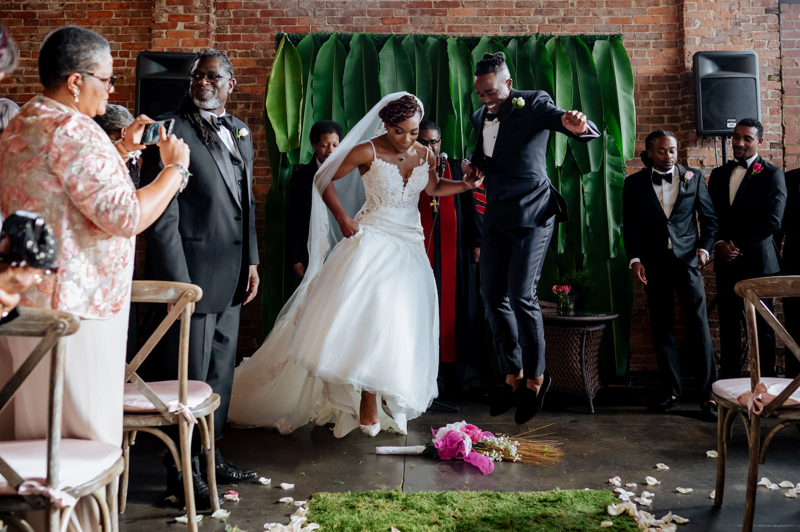 Tampa Wedding Jumping The Broom Tradition   Ivory Spaghetti Strap Scoop Back Lace and Tulle Mermaid Martina Liana Wedding Dress Bridal Gown with Cathedral Length Long Lace Edge Veil   Groom in Modern Navy Suit with Black Satin Lapel   Modern Ceremony Backdrop with Tropical Palm Leaves