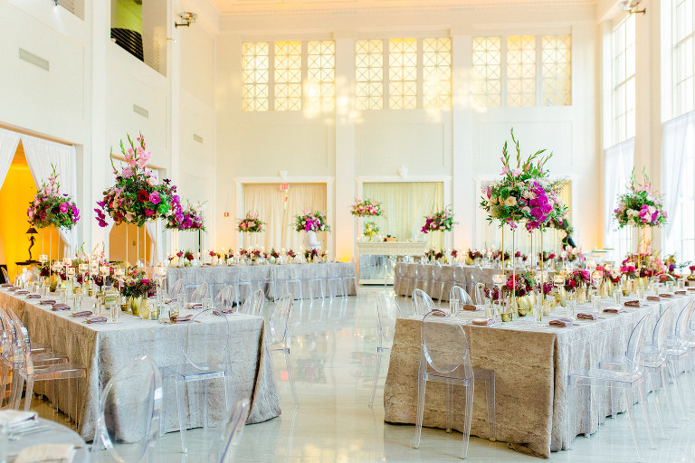 Colorful Luxury Indoor Wedding Reception at Tampa Wedding Venue The Vault | Feasting Tables with Ghost Chairs and Tall Centerpieces of Pink Gladiolas, Roses, Orchids and Greenery with Gold Bud Vases and Candles | Kate Ryan Event Rentals
