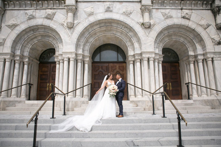 Outdoor Downtown Tampa Bride and Groom Portrait at Traditional Catholic Ceremony Cathedral Church Staircase | V Neck Illusion Lace A Line Ballgown Wedding Dress with Rhinestone Waist Band and Cathedral Veil | Groom in Classic Navy Blue Suit with Bow Tie | Blush Pink and Ivory Roses and Peonies Bridal Bouquet with Eucalyptus Greenery | Carrie Wildes Photography