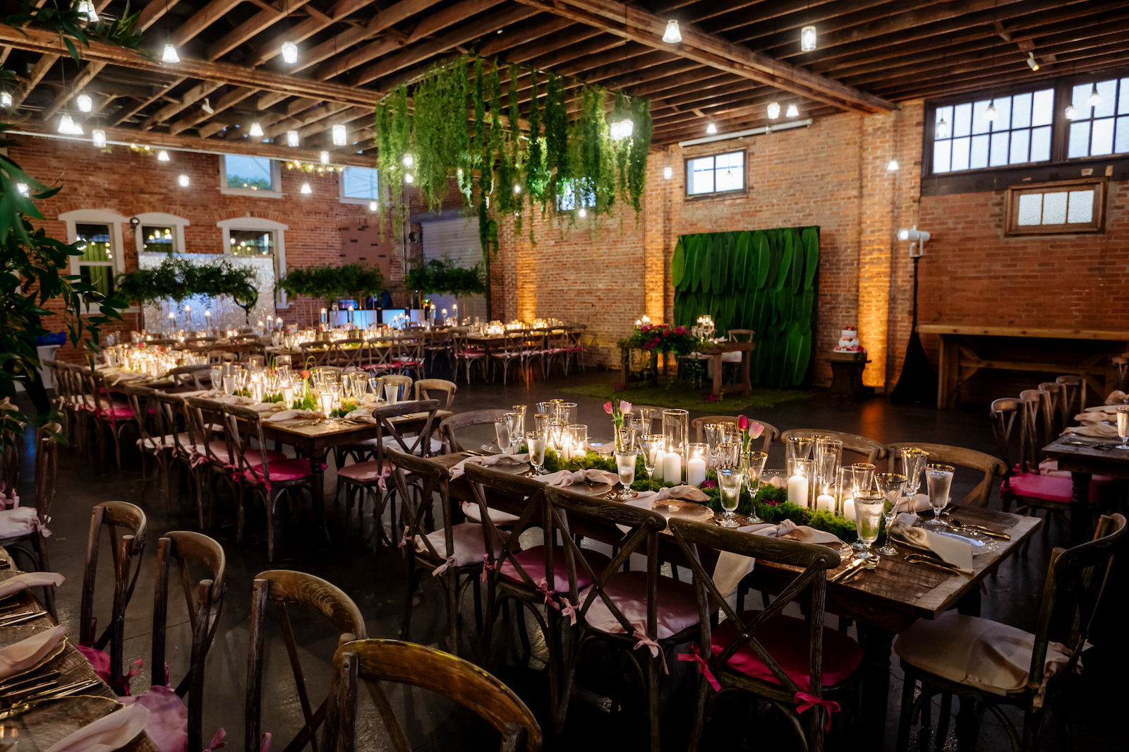 Modern Wedding Sweetheart Table Backdrop with Tropical Palm Leaves   Wood Cross Back Chairs with Ombre Pink Cushions in Historic Tampa Heights Venue with Brick Walls   Suspended Greenery Garland Ceiling Installment Wedding Floral Chandelier   Wood Farm Feasting Tables with Candles and Moss Wedding Reception Centerpieces   Kate Ryan Event Rentals