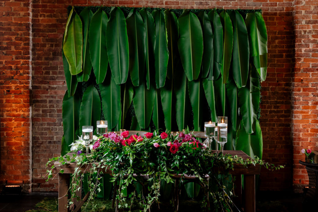 Modern Wedding Sweetheart Table Backdrop with Tropical Palm Leaves | Wedding Reception Sweetheart Table with Greenery and Pink Roses Arrangement and Floating Candles