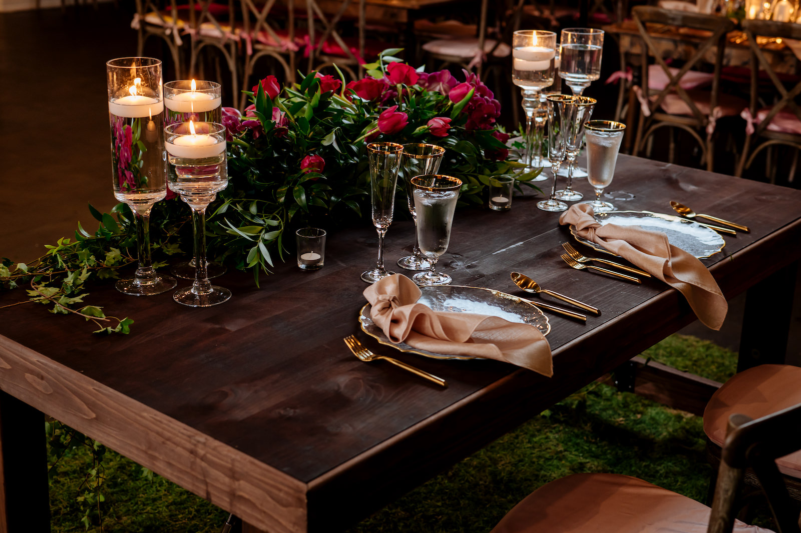 Wood Farm Wedding Reception Sweetheart Table with Greenery and Pink Roses Arrangement and Floating Candles   Wedding Reception Place Setting with Gold Rimmed Glassware and Gold Flatware with Gold Rim Glass Charger Plate by Kate Ryan Event Rentals   Kate Ryan Event Rentals