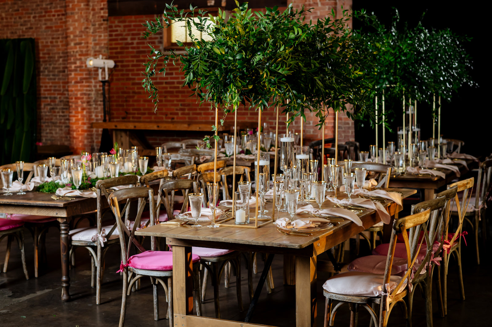Wood Cross Back Chairs with Ombre Pink Cushions in Historic Tampa Heights Venue with Brick Walls   Wood Farm Feasting Tables with Tall Greenery Centerpieces and Candles with Moss Centerpieces   Wedding Reception Place Setting with Gold Rimmed Glassware and Gold Flatware with Gold Rim Glass Charger Plate by Kate Ryan Event Rentals
