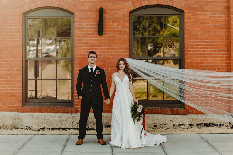 Bride and Groom Outdoor Wedding Portrait Veil Shot In Front Of Brick Wall | Charcoal Grey Wool Groom Suit with Burgundy Maroon Red Neck Tie | Wild Boho Loose Organic Greenery Bridal Bouquet with Ferns Blush Pink Roses and Protea and Red Amaranthus | Dewitt for Love Photography