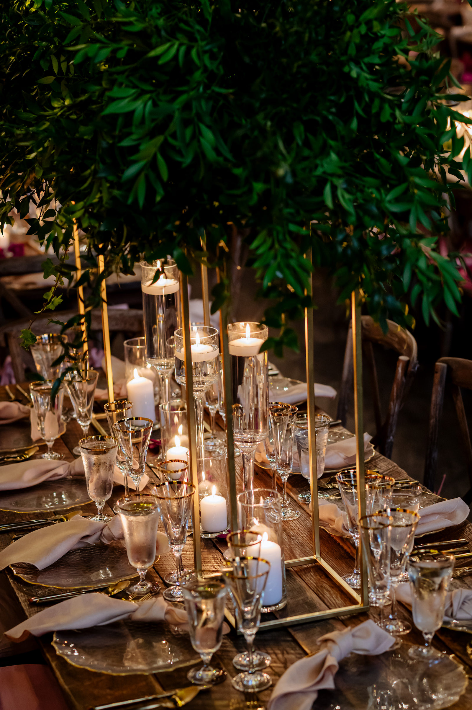 Wood Farm Feasting Tables with Tall Greenery Centerpieces and Candles   Tampa Wedding Reception Place Setting with Gold Rimmed Glassware and Gold Flatware with Gold Rim Glass Charger Plate by Kate Ryan Event Rentals