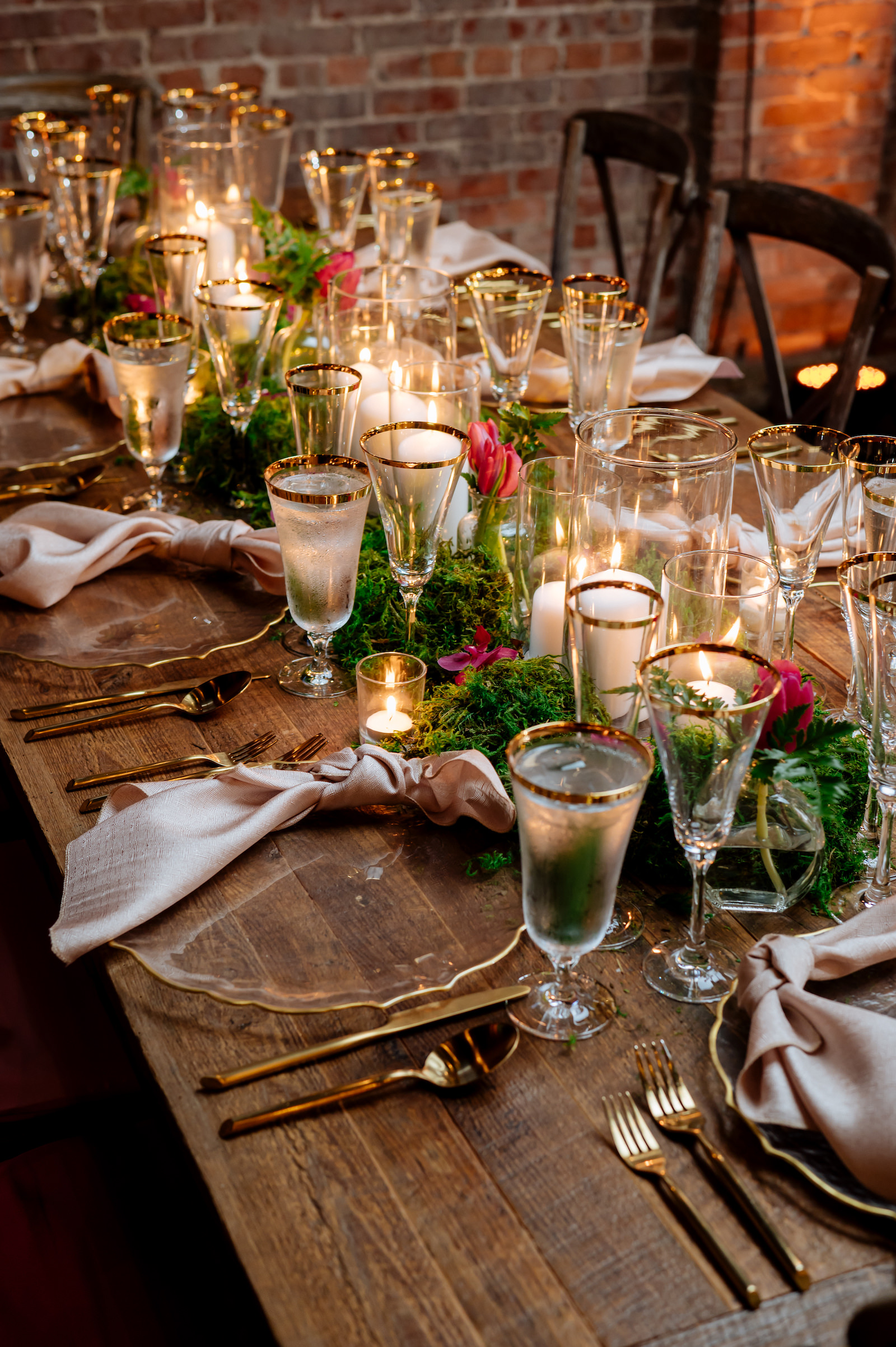 Wood Farm Feasting Tables with Moss Centerpieces with Pink Tulips and Candles   Tampa Wedding Reception Place Setting with Gold Rimmed Glassware and Gold Flatware with Gold Rim Glass Charger Plate by Kate Ryan Event Rentals