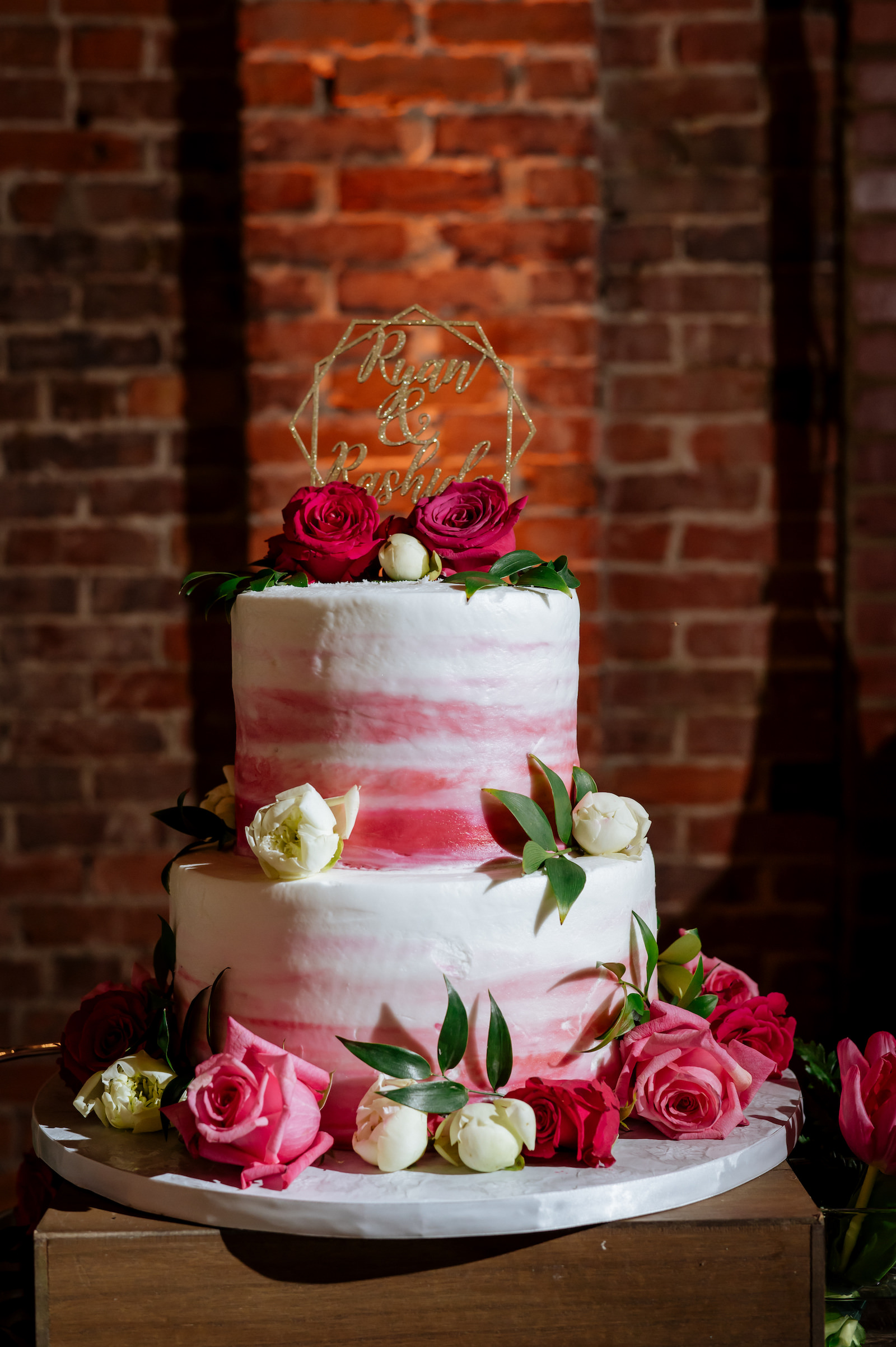 Two Tier Pink Ombre Wedding Cake with Pink and White Roses and Gold Glitter Geometric Cake Topper by Alessi Bakery