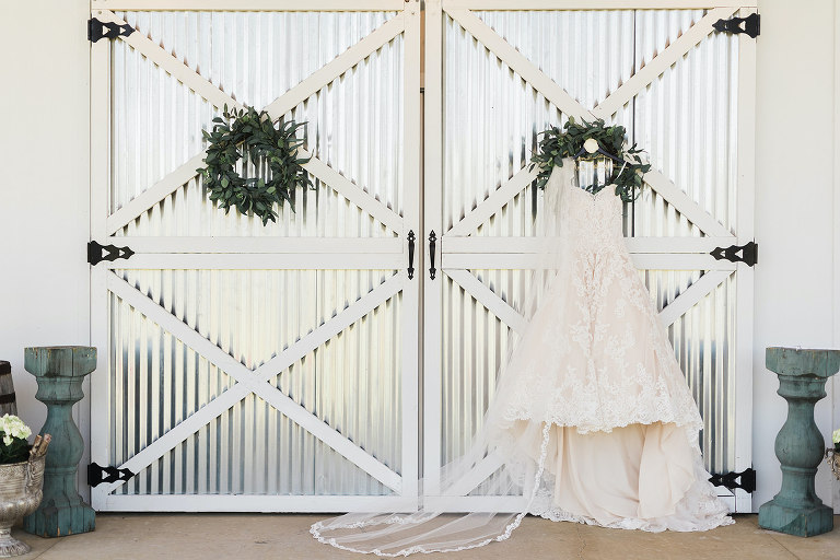 Rustic Inspired Bridal Details, Strapless Lace A A-Line Morilee Wedding Dress Hanging from Steel Barn Door | Florida Wedding Planner and Designer John Campbell Weddings