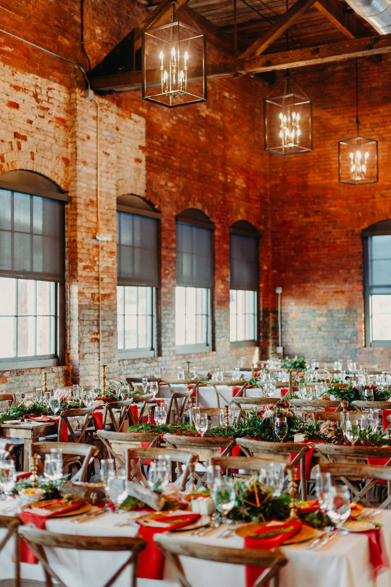 Tampa Wedding Reception at Historic Building Armature Works with Brick Walls and Industrial Chic Chandeliers | Long Feasting Tables with Wood Cross Back Chairs and Greenery Garland Runners with Burgundy Maroon Red Napkins