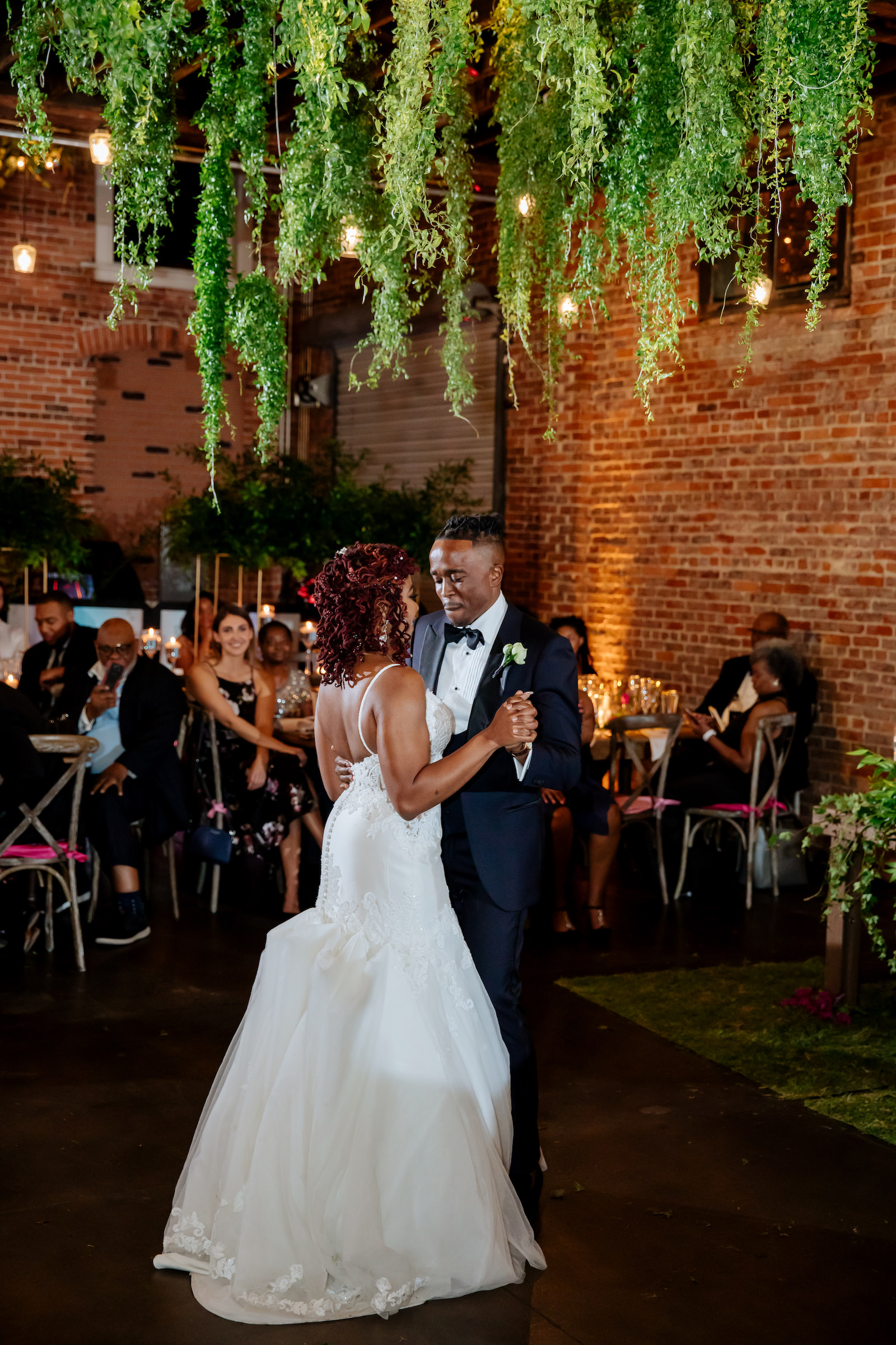 Bride and Groom First Dance at Tampa Heights Wedding Reception in Historic Venue with Brock Walls   Suspended Greenery Garland Ceiling Installment Wedding Floral Chandelier