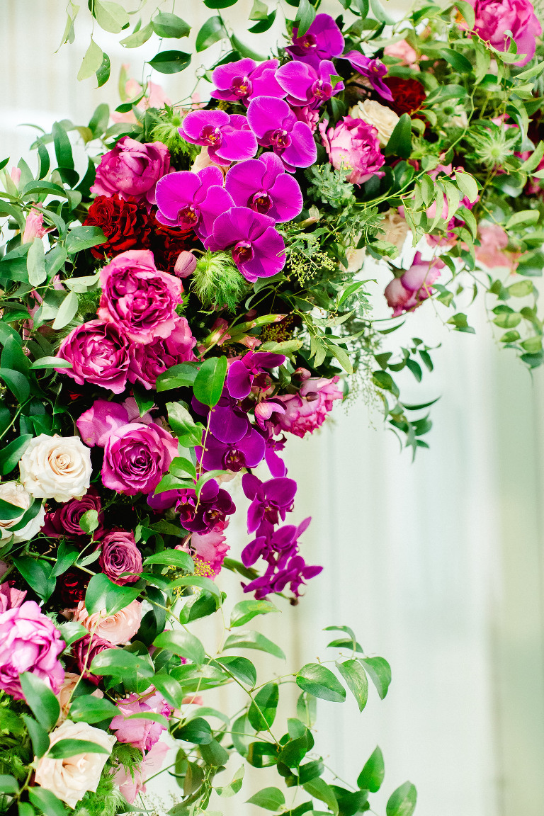 Bright Colorful Florida Wedding Ceremony Floral Arch with Pink Roses and Purple Orchids and Greenery