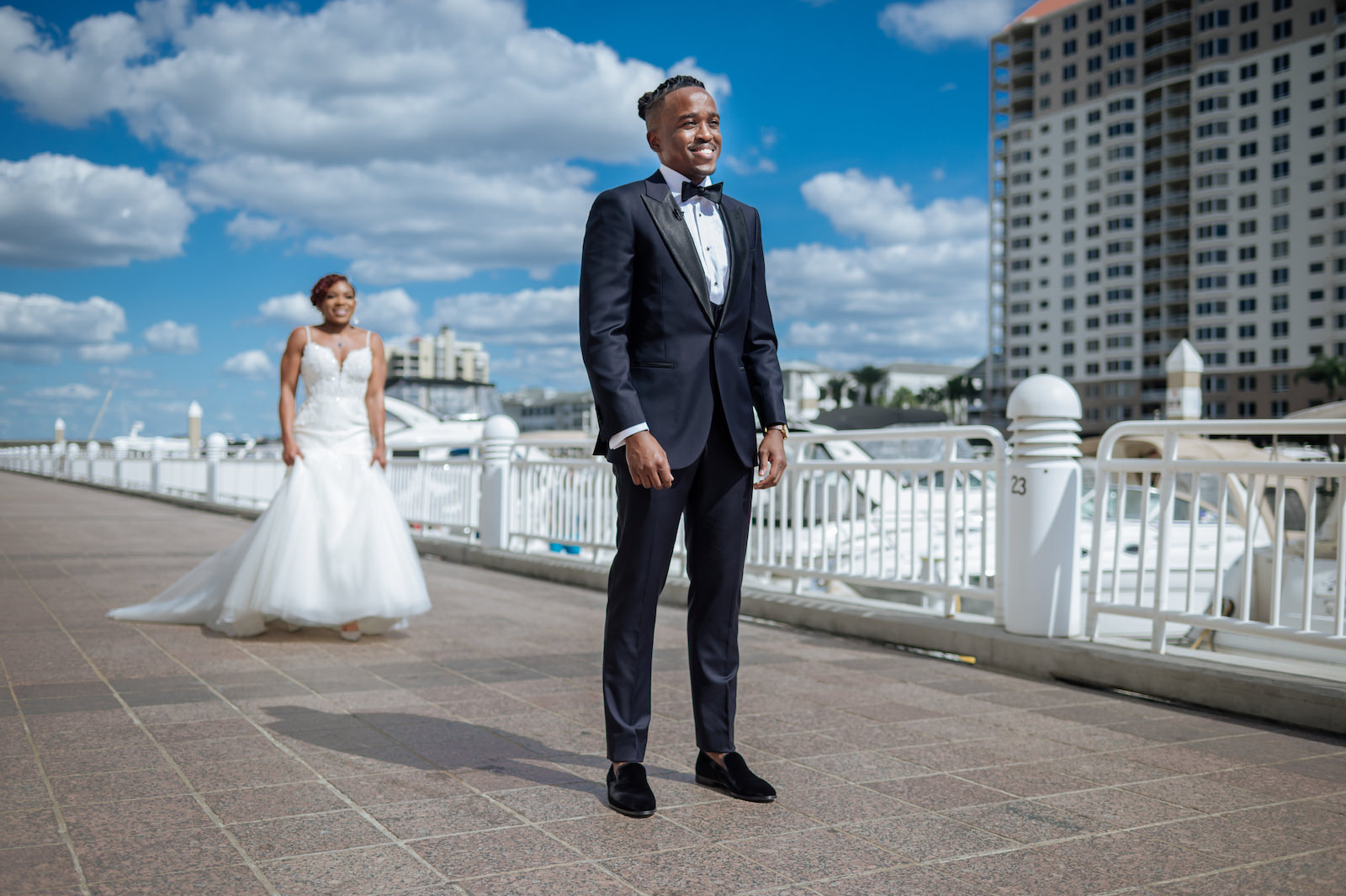 Bride and Groom Outdoor First Look along Marina in Downtown Tampa Channelside   Groom in Modern Navy Suit with Black Satin Lapel and Bow Tie