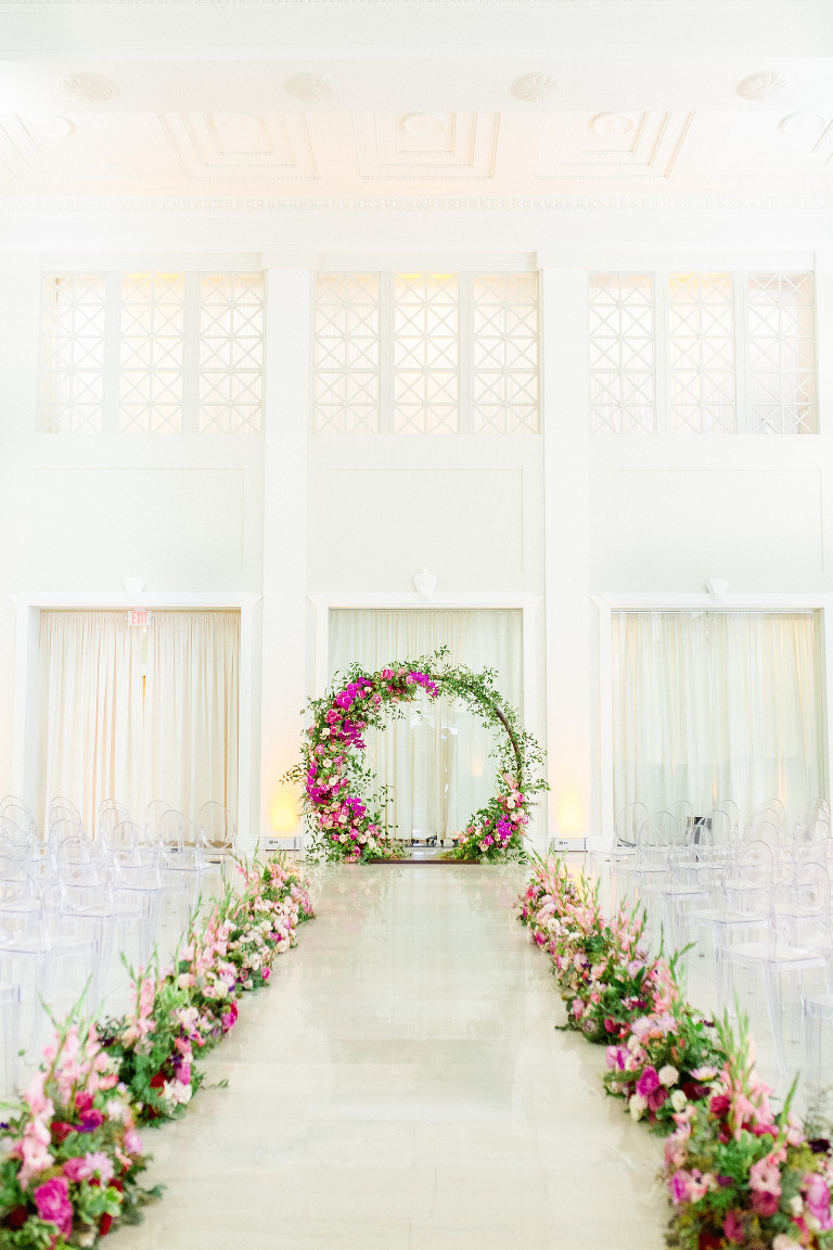 Indoor Downtown Tampa Wedding Ceremony at Tampa Wedding Venue The Vault | Bright Colorful Florida Wedding Ceremony Floral Circle Moon Round Arch with Pink Roses and Purple Orchids and Greenery | Ceremony Aisle Flowers with Blush Pink Gladiolas | Clear Ghost Chairs from Kate Ryan Event Rentals