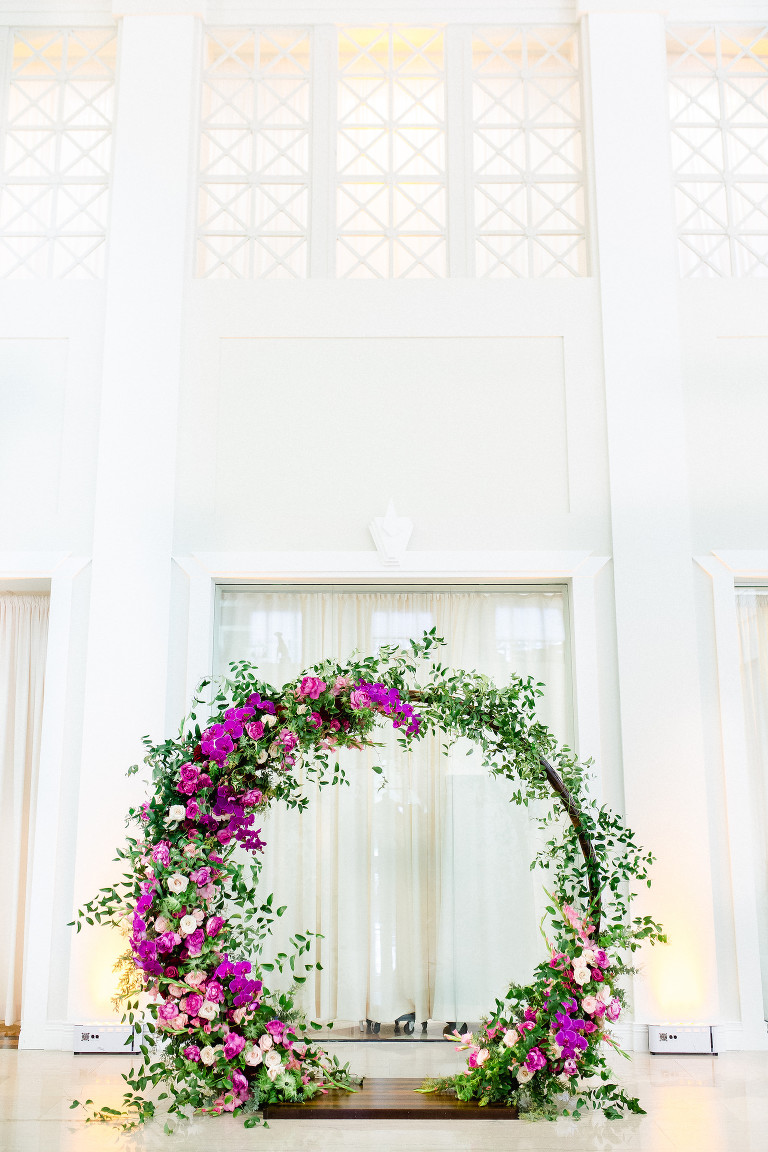 Indoor Downtown Tampa Wedding Ceremony at Tampa Wedding Venue The Vault | Bright Colorful Florida Wedding Ceremony Floral Circle Moon Round Arch with Pink Roses and Purple Orchids and Greenery