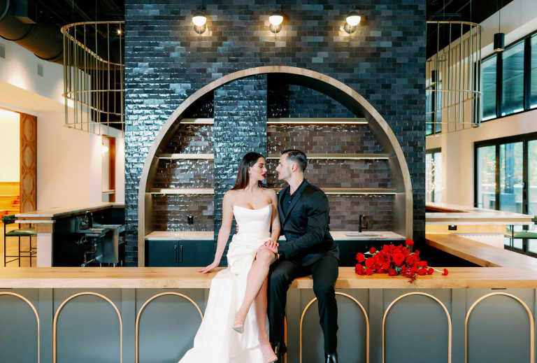 Modern Indoor South Tampa Wedding Space at Tampa Wedding Venue Hyde House   Dramatic Modern Ines di Santo High Slit Wedding Dress by Isabel Oneil Bridal   Groom in All Black Suit   Modern Dramatic Unique Asymmetrical Red Wedding Bridal Bouquet with Ranunculus Tulips Protea Roses Anemone and Amaryllis