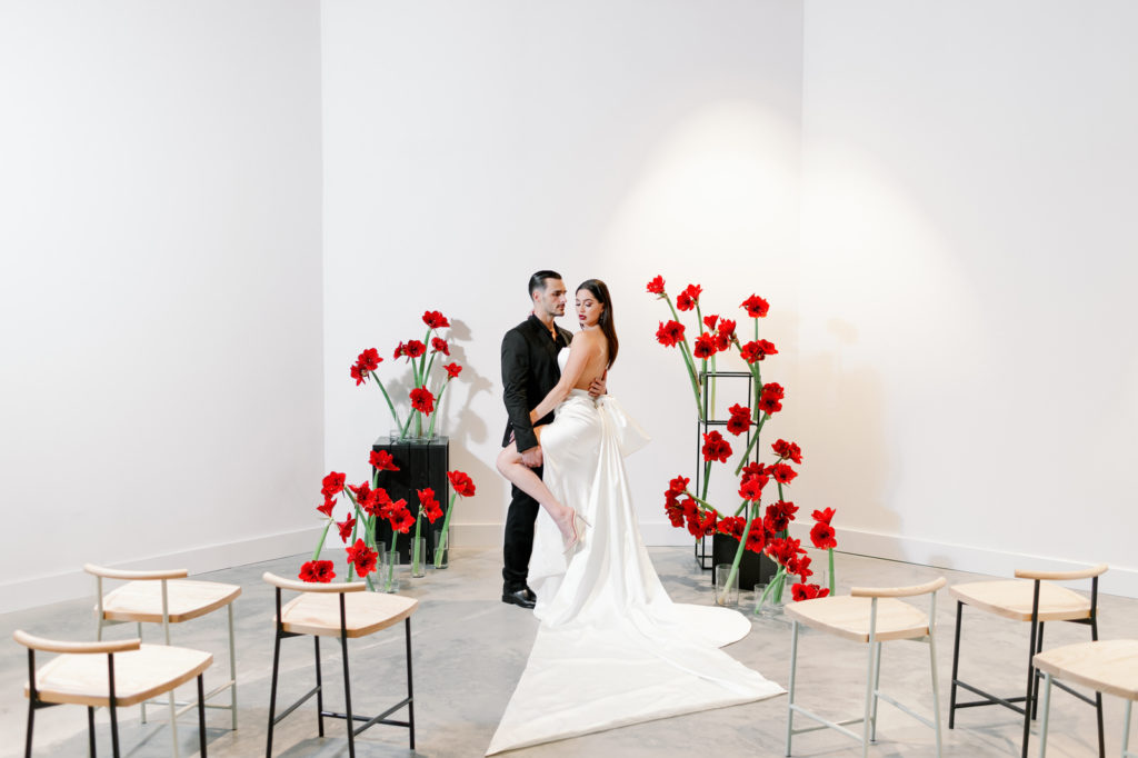 Modern Clean Indoor Ceremony Space at Tampa Wedding Venue Hyde House | Black White and Red Ceremony Backdrop with Red Amaryllis and Black Columns | Dramatic Modern Ines di Santo High Slit Wedding Dress by Isabel Oneil Bridal | Groom in All Black Suit | Black and White Birch Ceremony Chairs