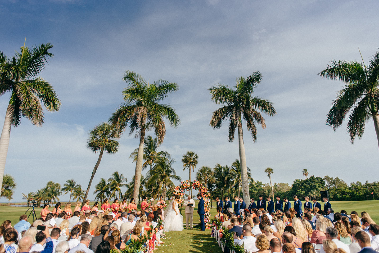 Tropical Wedding Ceremony Decor, Colorful Pink and Coral Floral Arch, Bride and Groom Exchanging Vows   Boca Grande Wedding Venue Gasparilla Inn   Tampa Bay Wedding Planner NK Weddings
