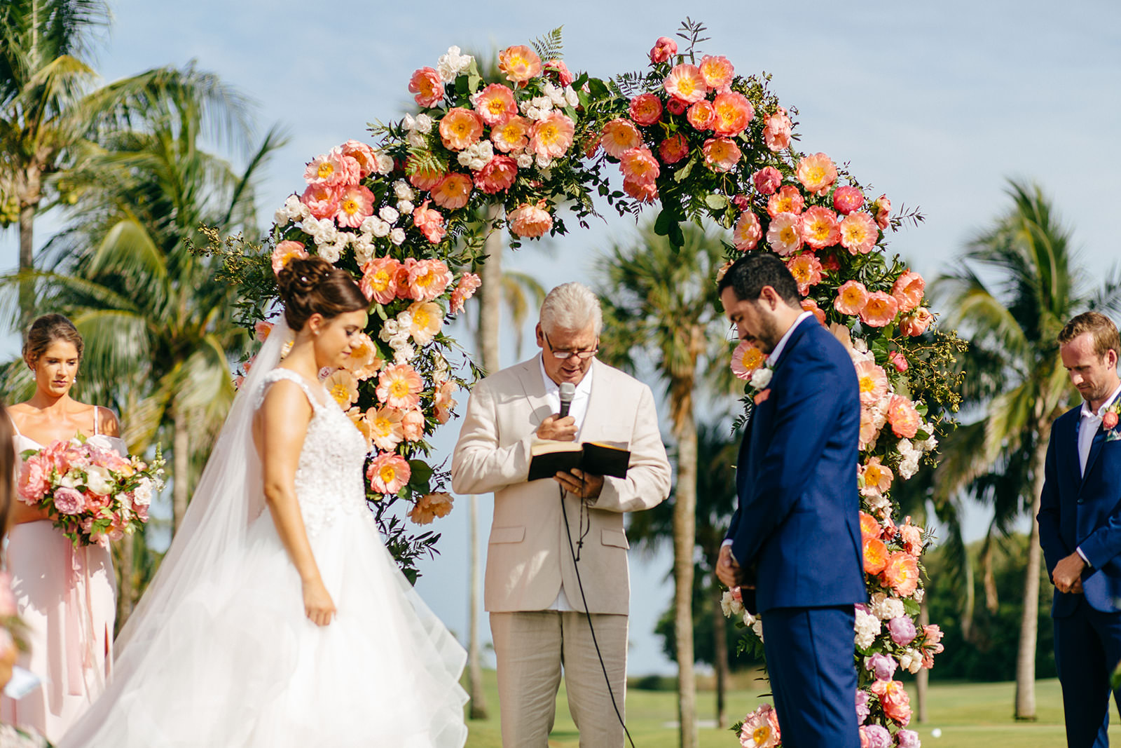 Bride and Groom Praying During Wedding Ceremony, Tropical Colorful Pink and Coral Floral and Palm Tree Leaves Lush Arch   Tampa Bay Wedding Planner NK Weddings