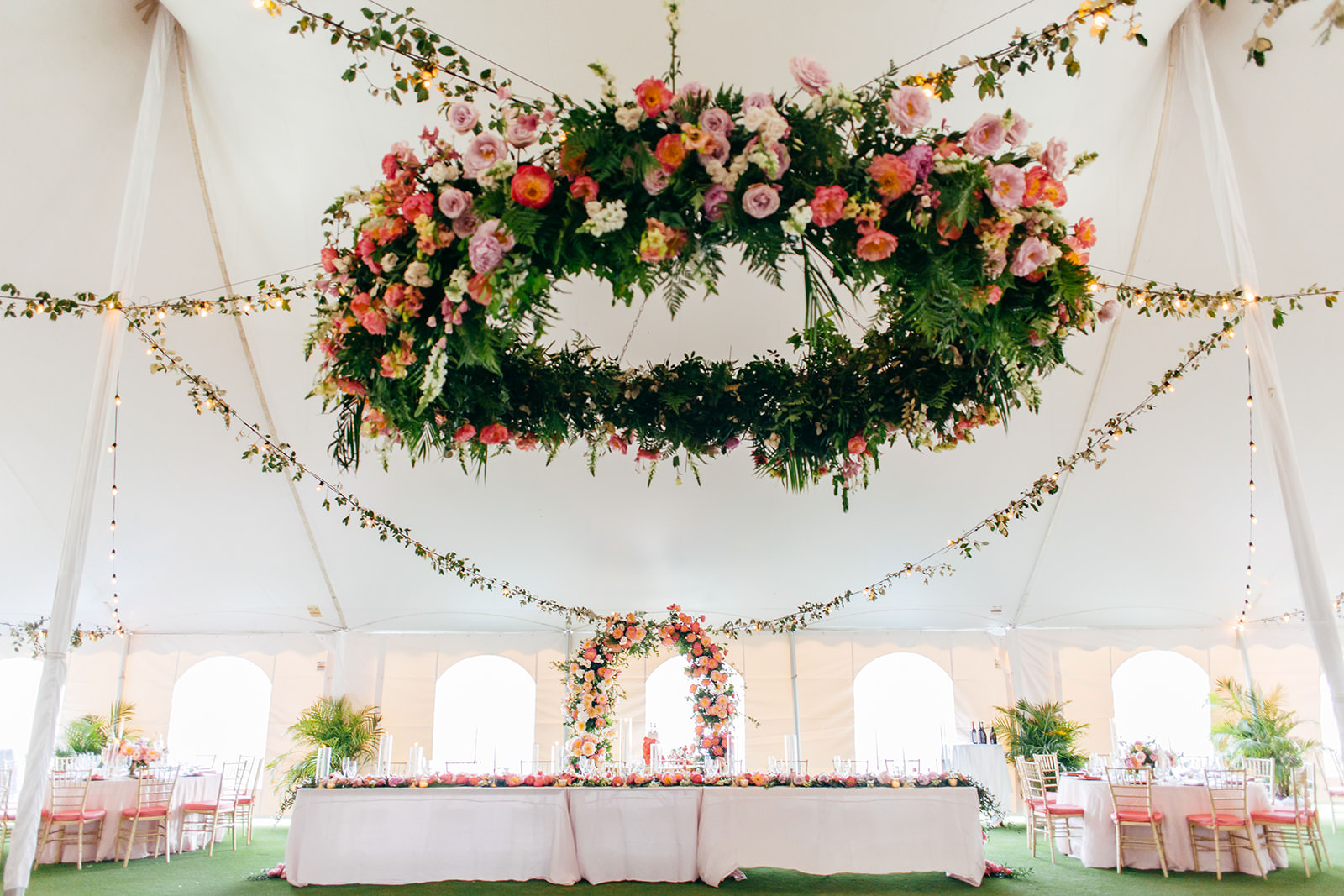 Tropical Elegant Tent Wedding Reception Decor, Lush Pink, Coral, Purple and Palm Tree Leaves Lush Floral Chandelier and Hanging Florals, Long Feasting Table with White Linens, Colorful Floral Arch Behind Sweetheart Table   Tampa Bay Wedding Planner NK Weddings