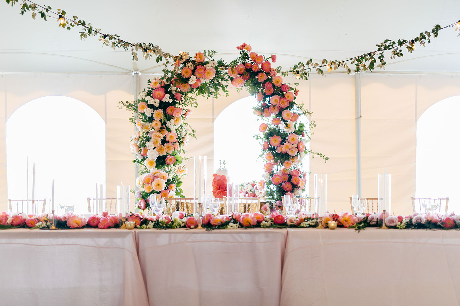Elegant Tropical Tent Wedding Reception Decor, Lush Coral, Pink and Palm Tree Leaves Lush Floral Arch Behind Sweetheart Table, Hanging Flowers   Tampa Bay Wedding Planner NK Weddings