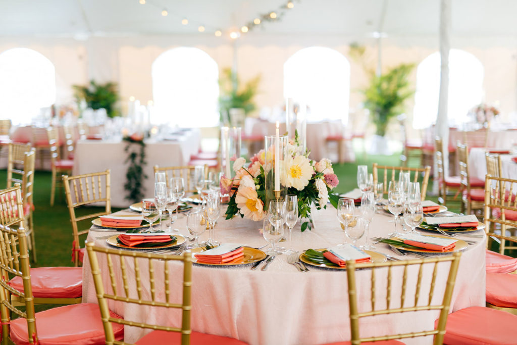 Elegant Tropical Tent Wedding Reception Decor, Round Table with Gold Chargers, Pink Linen Napkin, Colorful Low Floral Centerpieces, Gold Chiavari Chairs with Coral Cushions   Tampa Bay Wedding Planner NK Weddings