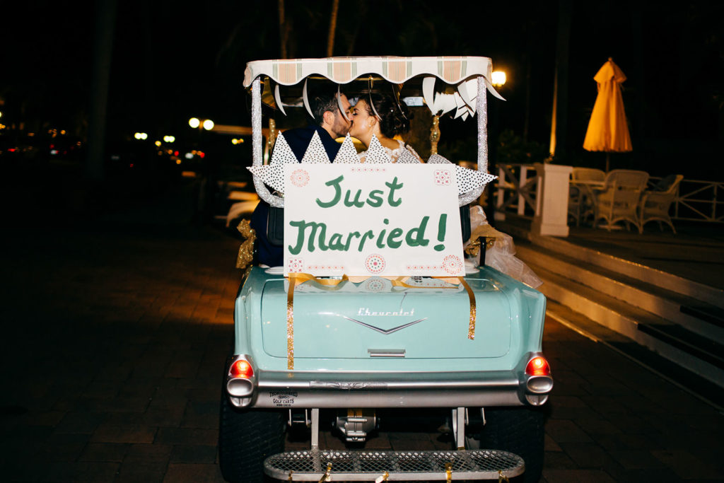 Bride and Groom Kissing on Aqua Vintage Car with Just Married Sign