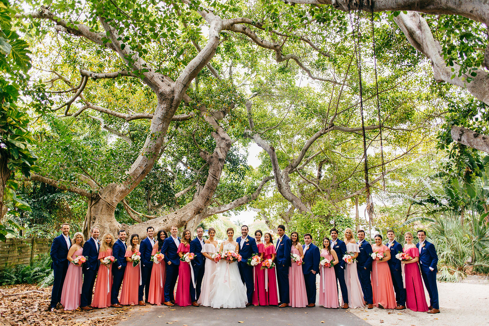 Tropical Colorful Wedding Party, Bridesmaids in Pink and Coral Dresses, Groomsmen in Navy Blue Suits