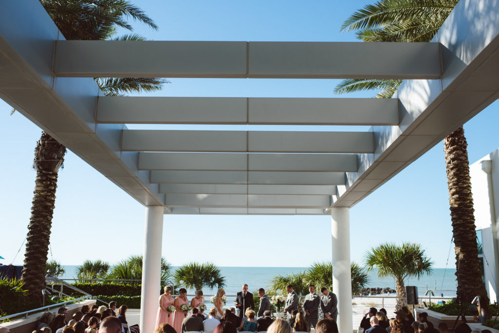 Outdoor Wedding Ocean View Waterfront Ceremony at Clearwater Beach Hotel Patio with White Garden Chairs, Pergola, and Fountain
