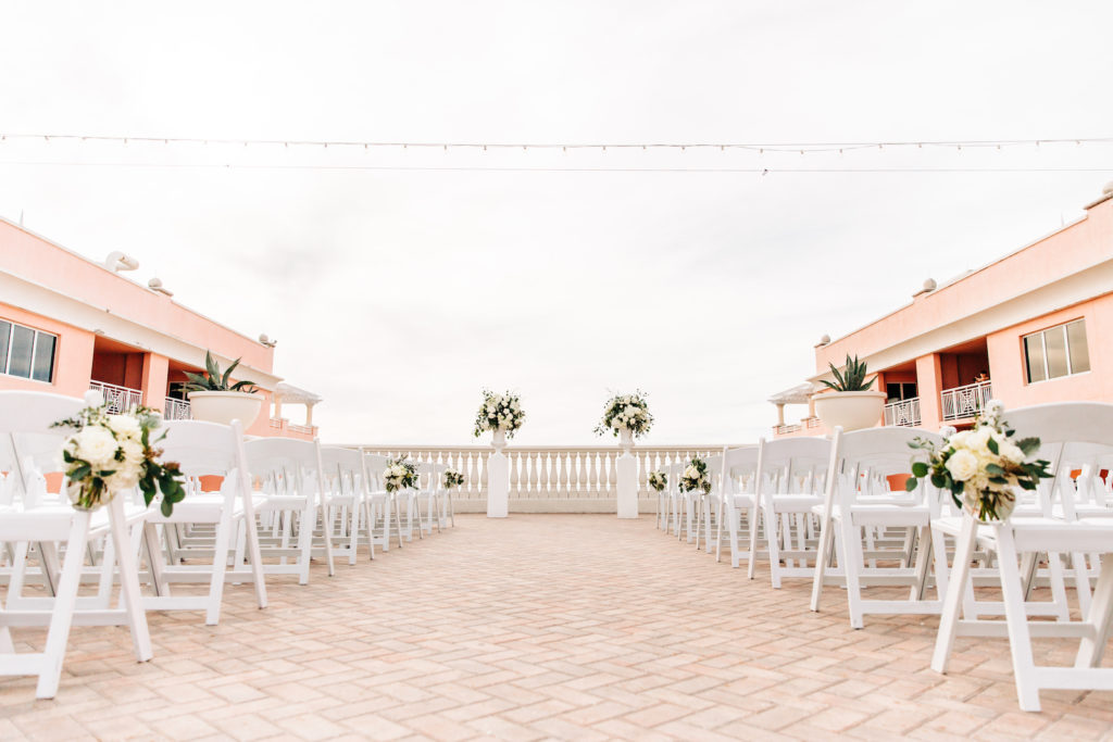 Waterfront Romantic Outdoor Wedding Ceremony and Decor, Rooftop Vow Exchange on Balcony, Decorated with Lush Floral Arrangements, with Ivory Roses, White Hydrangeas, and Greenery on Tall White Pedestals | Florida Beachfront Destination Wedding Venue Hyatt Regency Clearwater Beach | Tampa Bay Wedding Planner Special Moments Event Planning | St. Petersburg Florist Bruce Wayne Florals