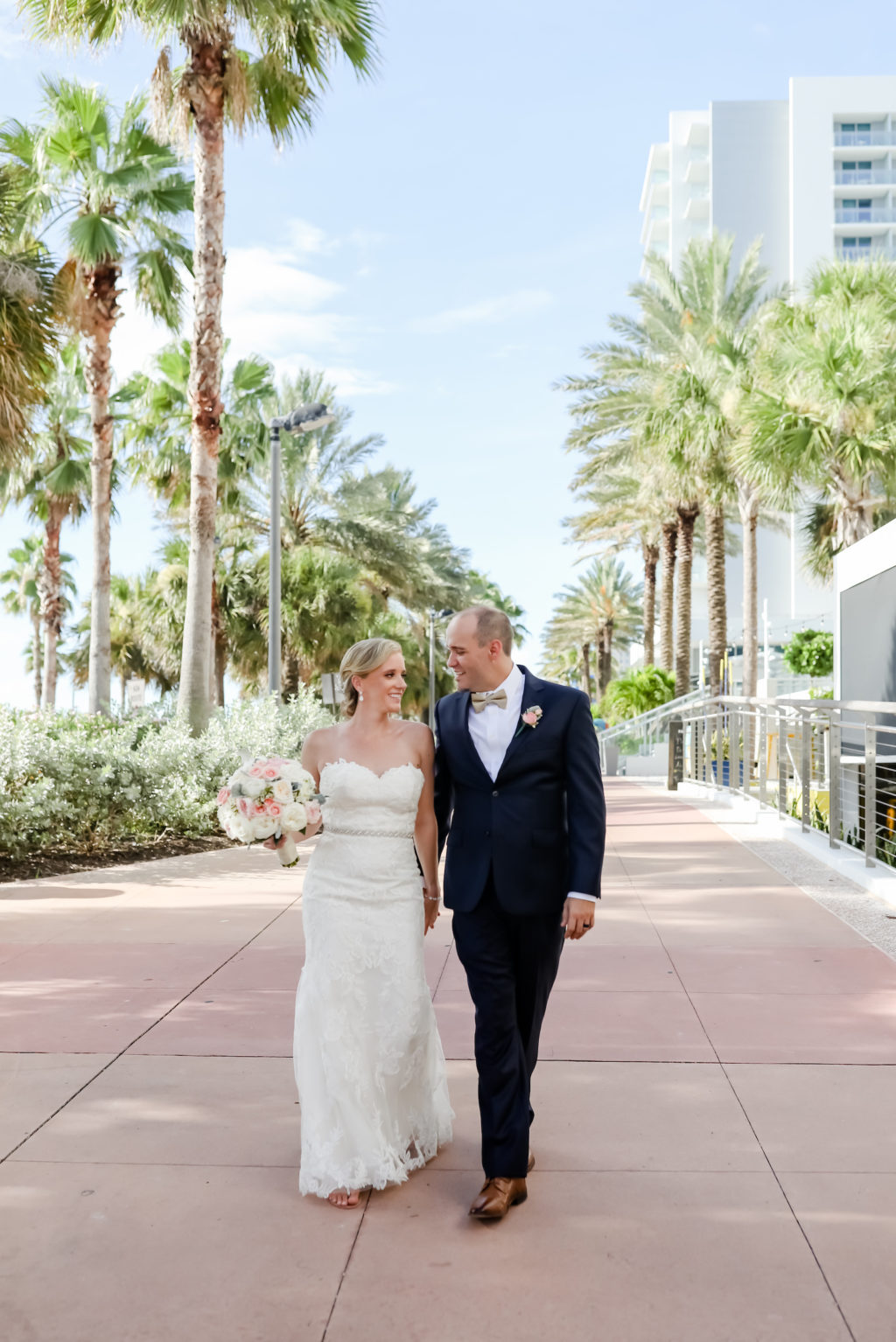 Bride and Groom Outdoor Portrait at Clearwater Beach Wedding | Bridal Gown Hanger Shot | Strapless Sweetheart Lace A Line Wedding Dress with Rhinestone Waistband | Blush Pink and White Rose Bouquet | Groom in Classic Navy Blue Suit with Champagne Bow Tie | Lifelong Photography Studios